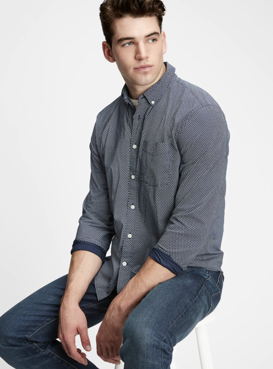 Model wearing button-up shirt with navy geo print