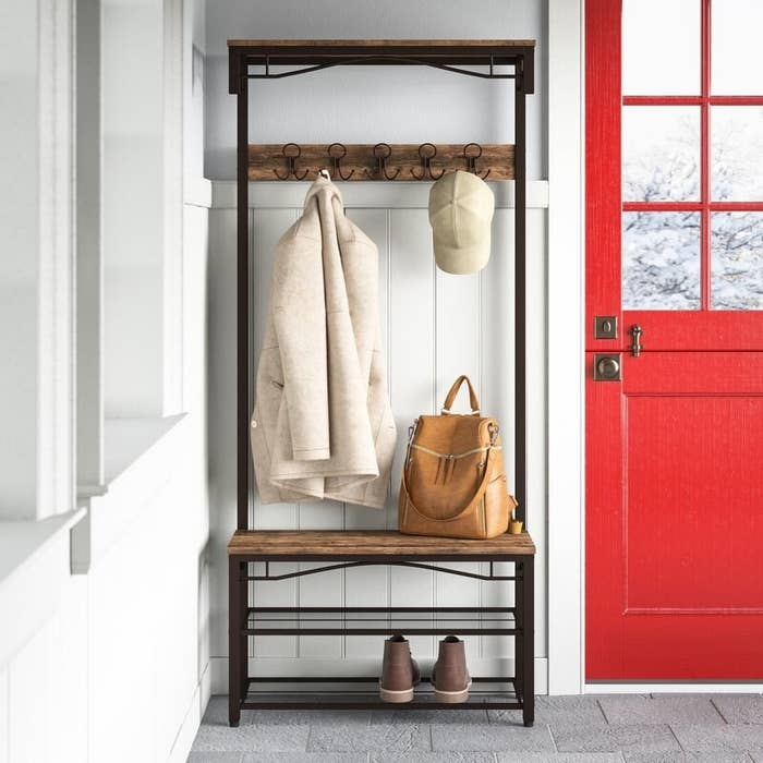 coat rack in picture with shoes, bag, coat, and hat.