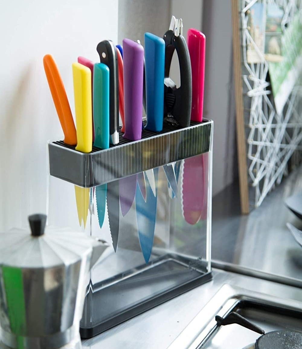 The transparent knife block on a counter filled with blades of different shapes and sizes