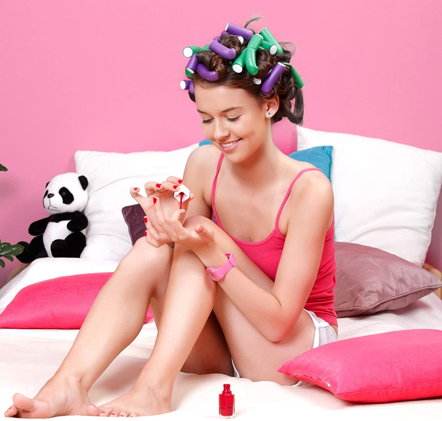 A person doing their nails on their bed with their hair in the curling rods