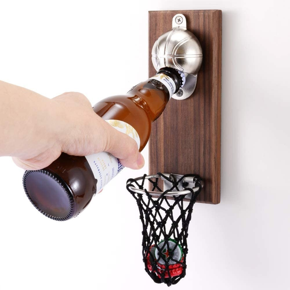 A person cracking open a beer with the bottle opener
