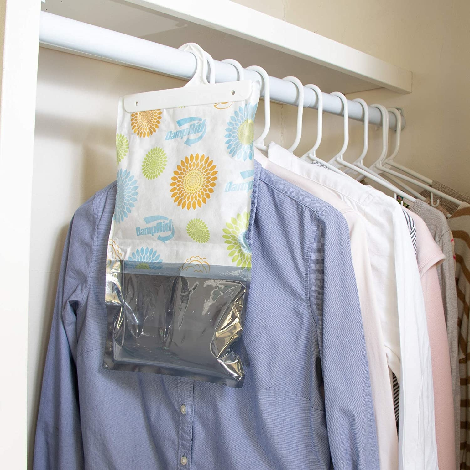A moisture-absorbing bag hanging on a closet rod in front of shirts