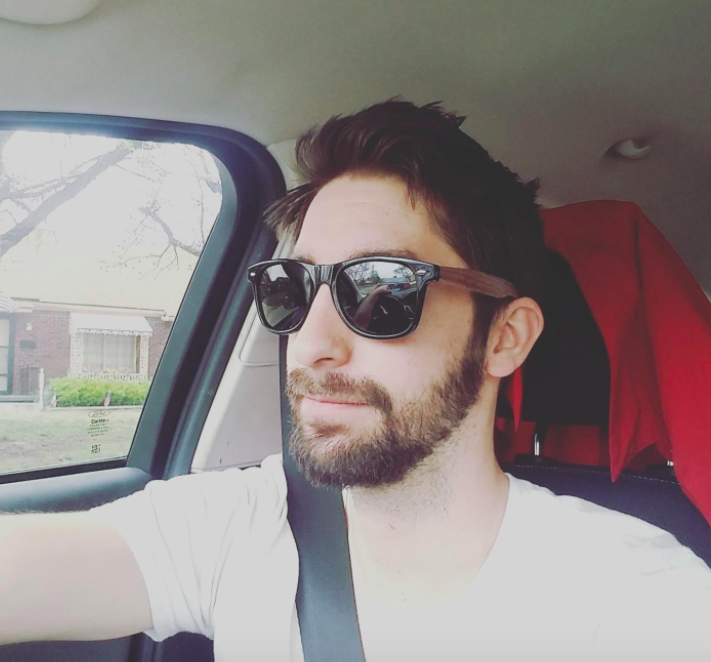reviewer wearing Woodies sunglasses while driving a car