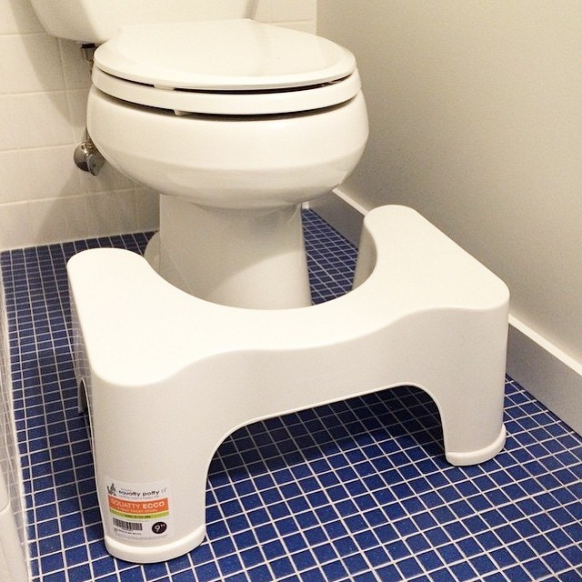 A small stool sitting in front of a toilet