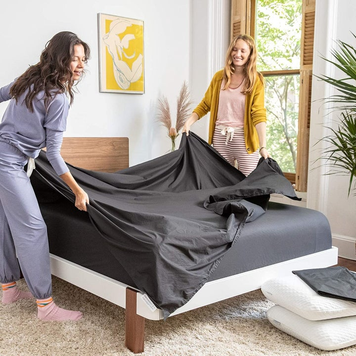 Two models putting a sheet on the mattress