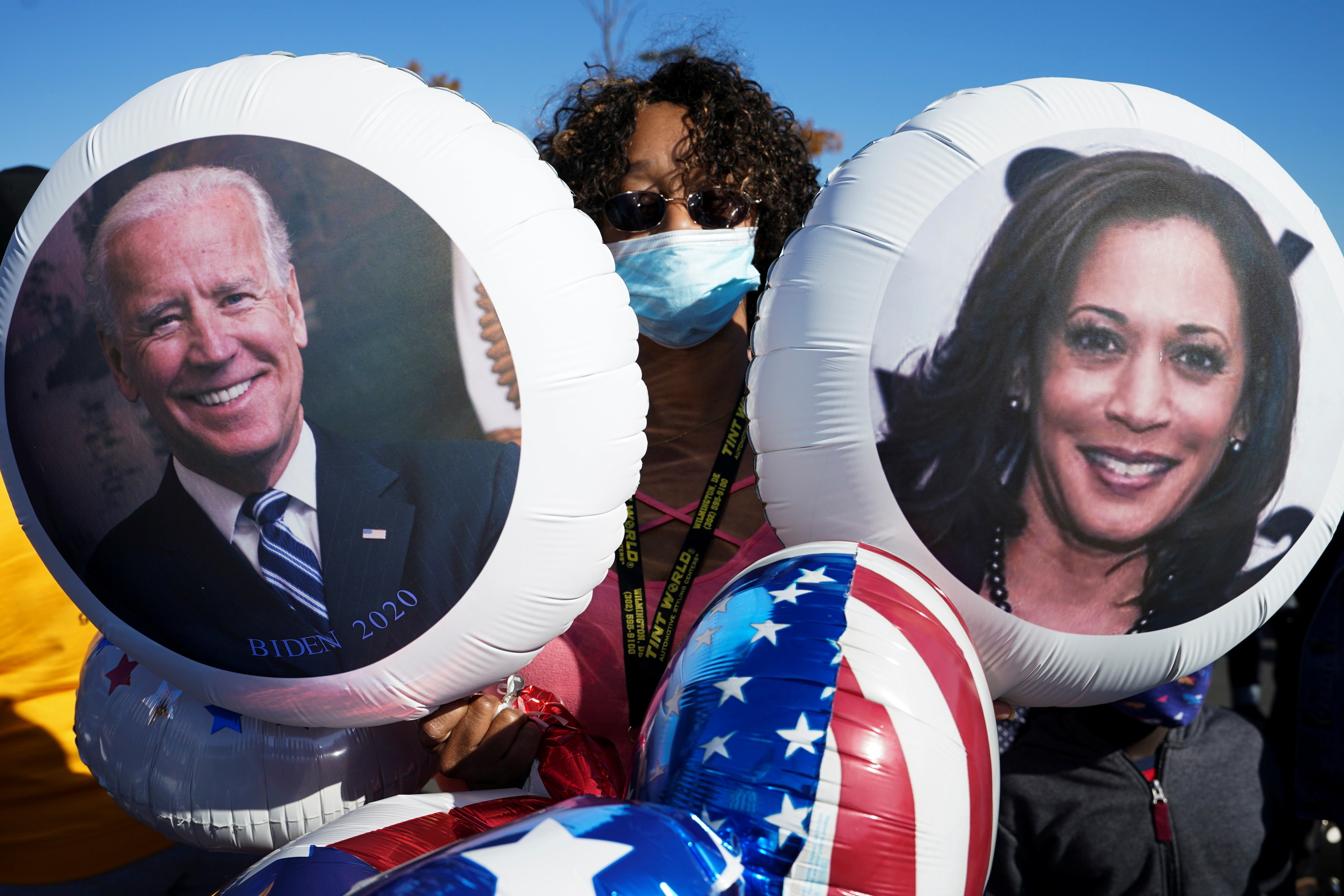 Someone holds up two balloons with Kamala Harris's and Joe Biden's faces on them