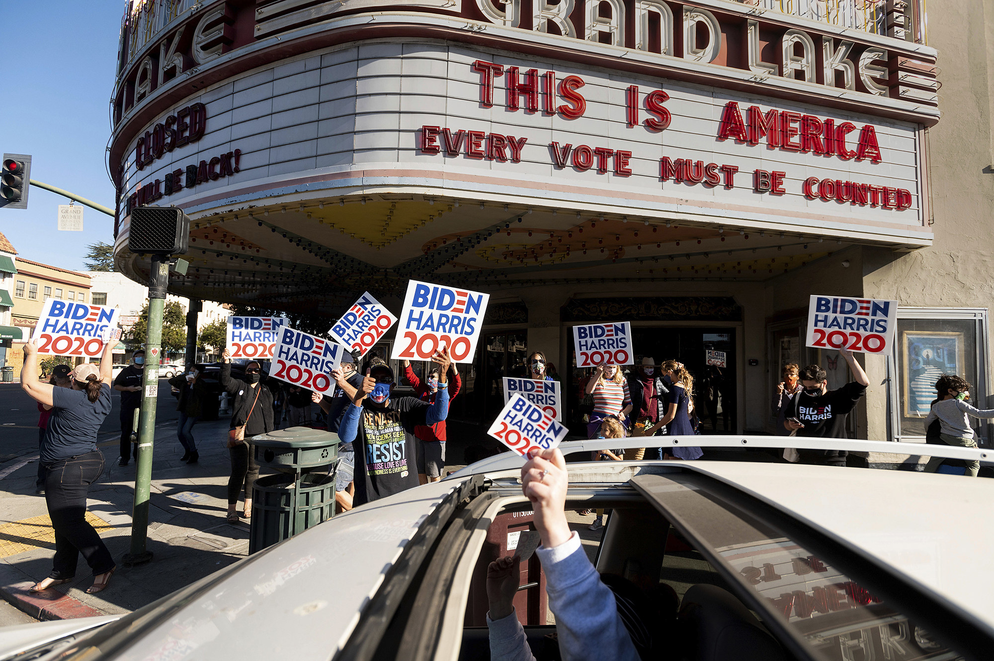 "People carrying ""Biden–Harris 2020"" signs celebrate under a theater marquee that reads ""This is America, every vote must be counted"""