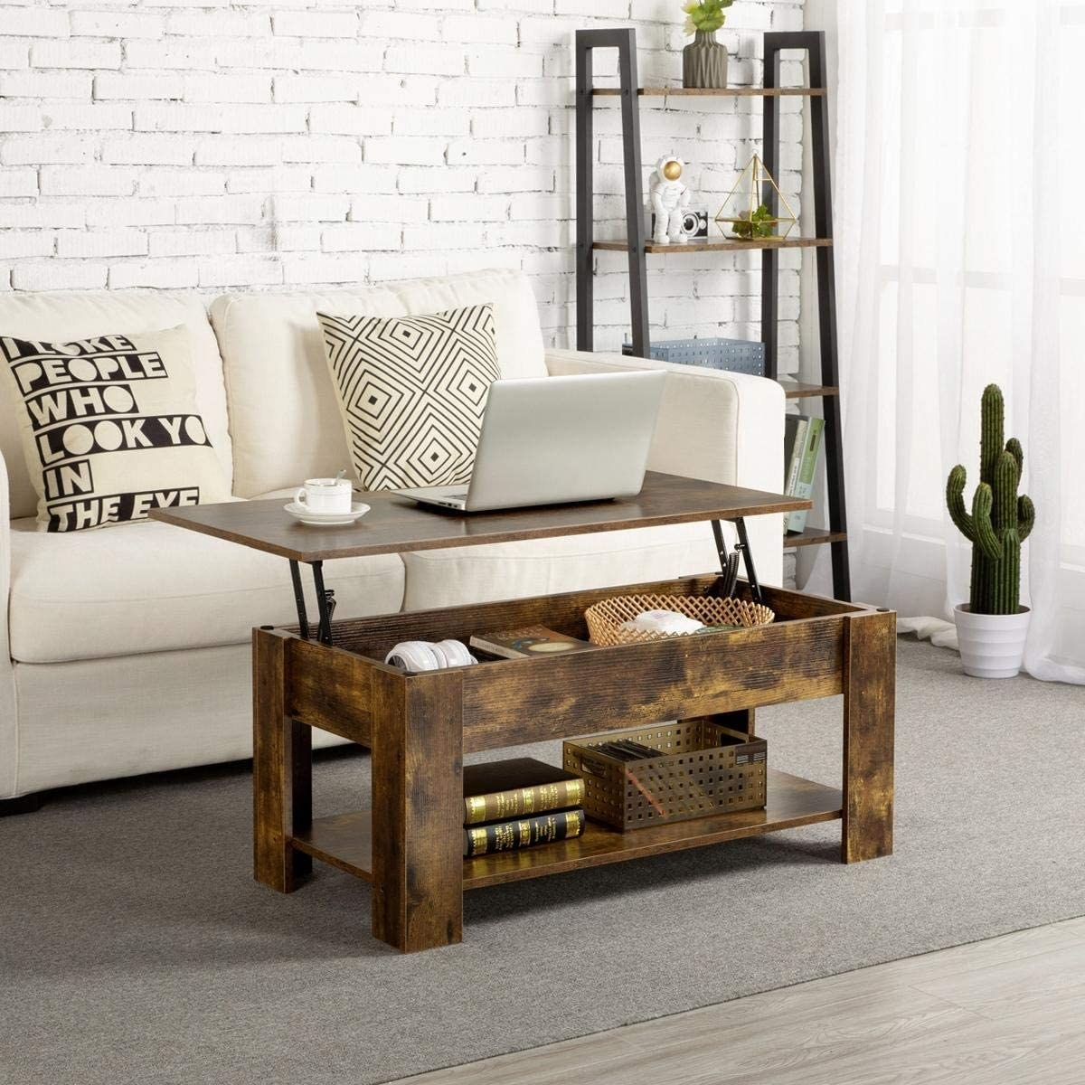 The dark wood coffee table with the top lifted and a laptop and mug on it