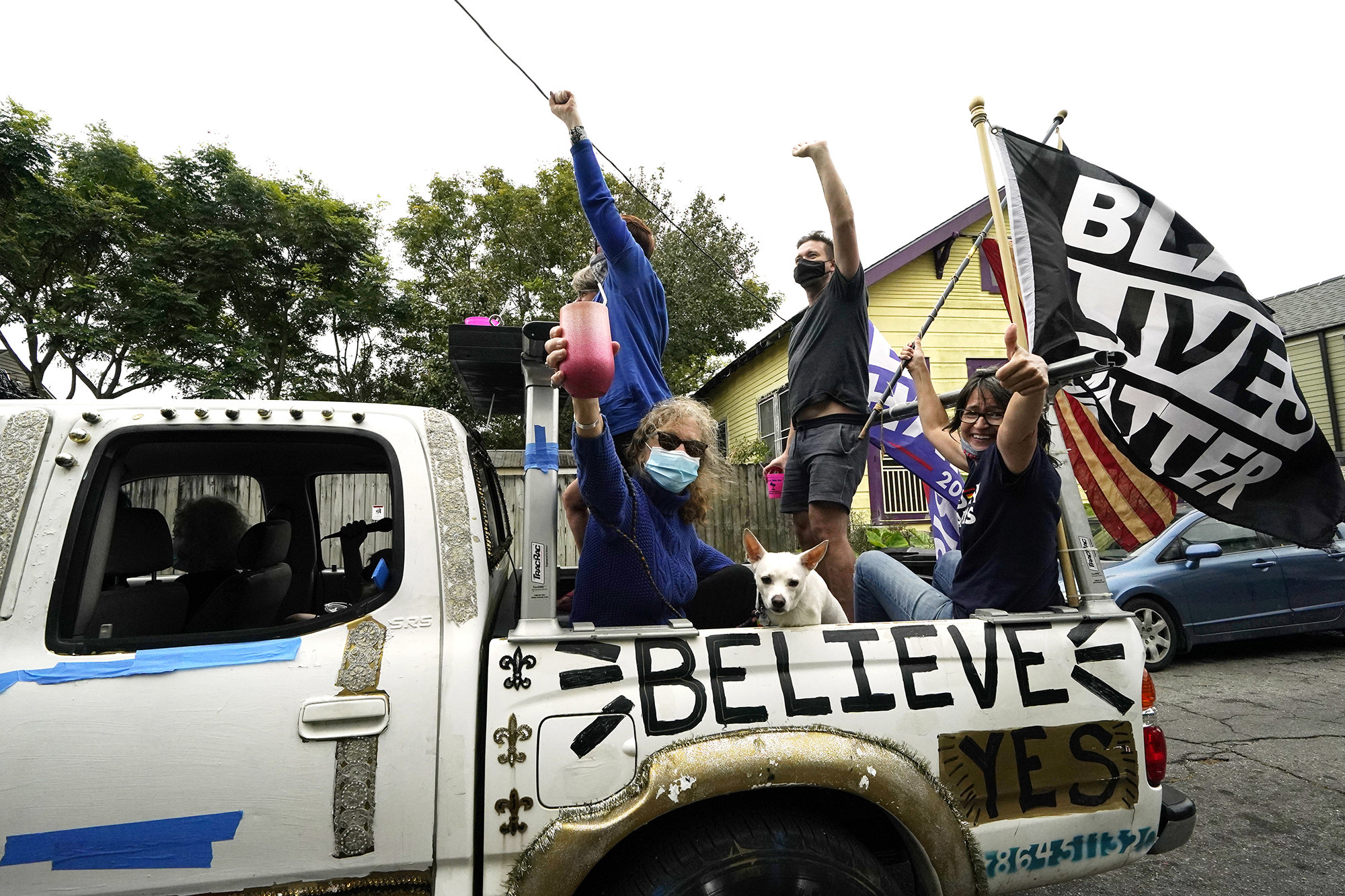 People raise their fists, smile, and raise a glass in the back of a pickup truck, where a Black Lives Matter flag waves