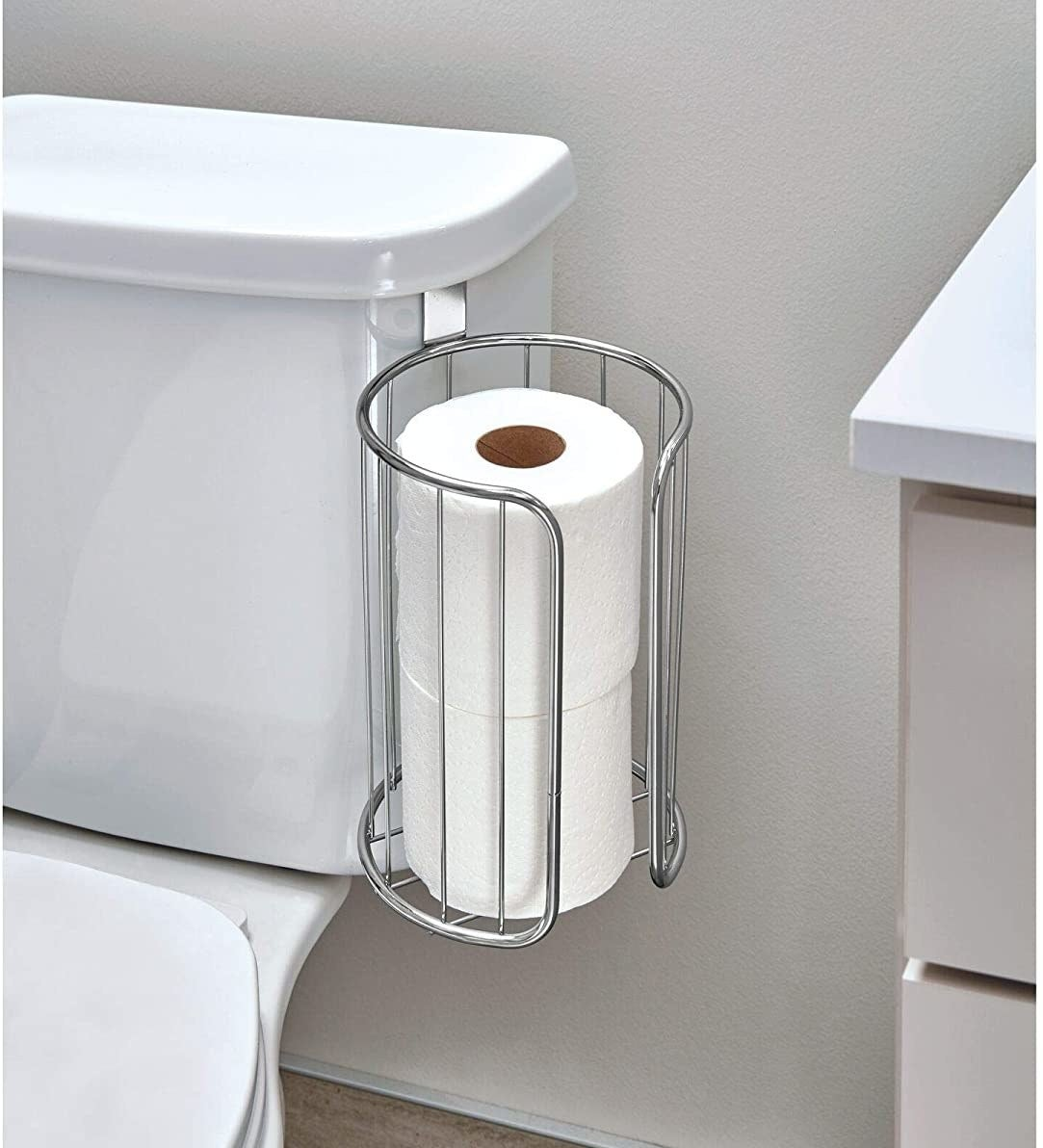 The toilet paper holder clipped to the tank of a toilet
