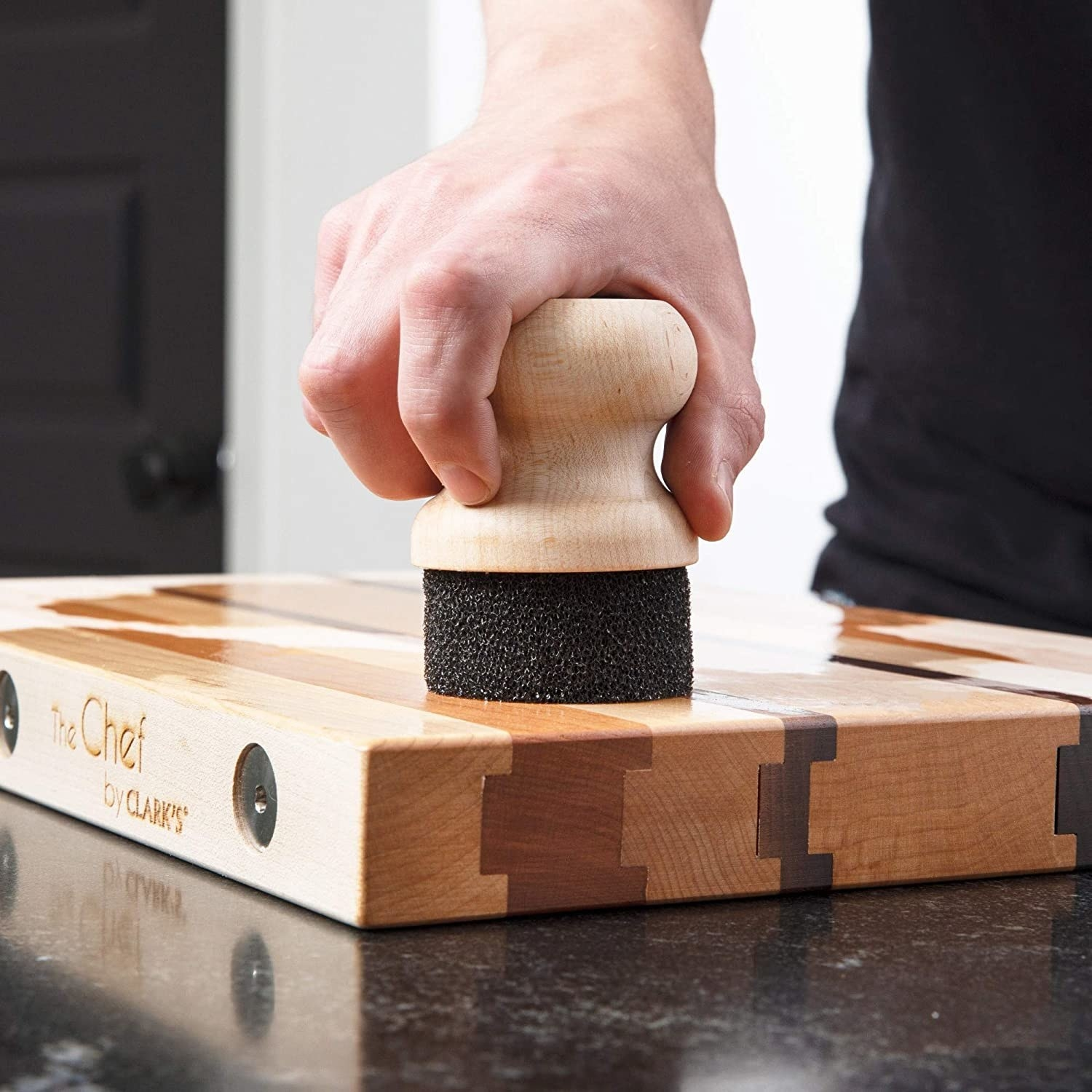 A person using the applicator to clean a cutting board