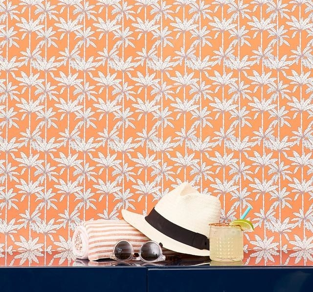 The orange wallpaper with white palm trees on it