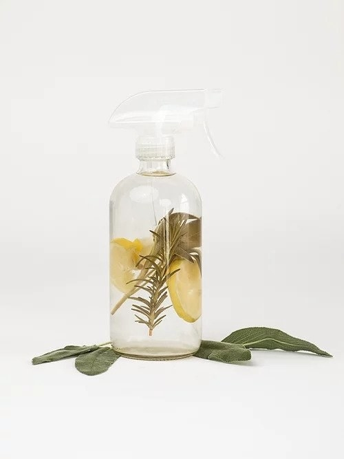 glass spray bottle filled with rosemary, sage, and lemon
