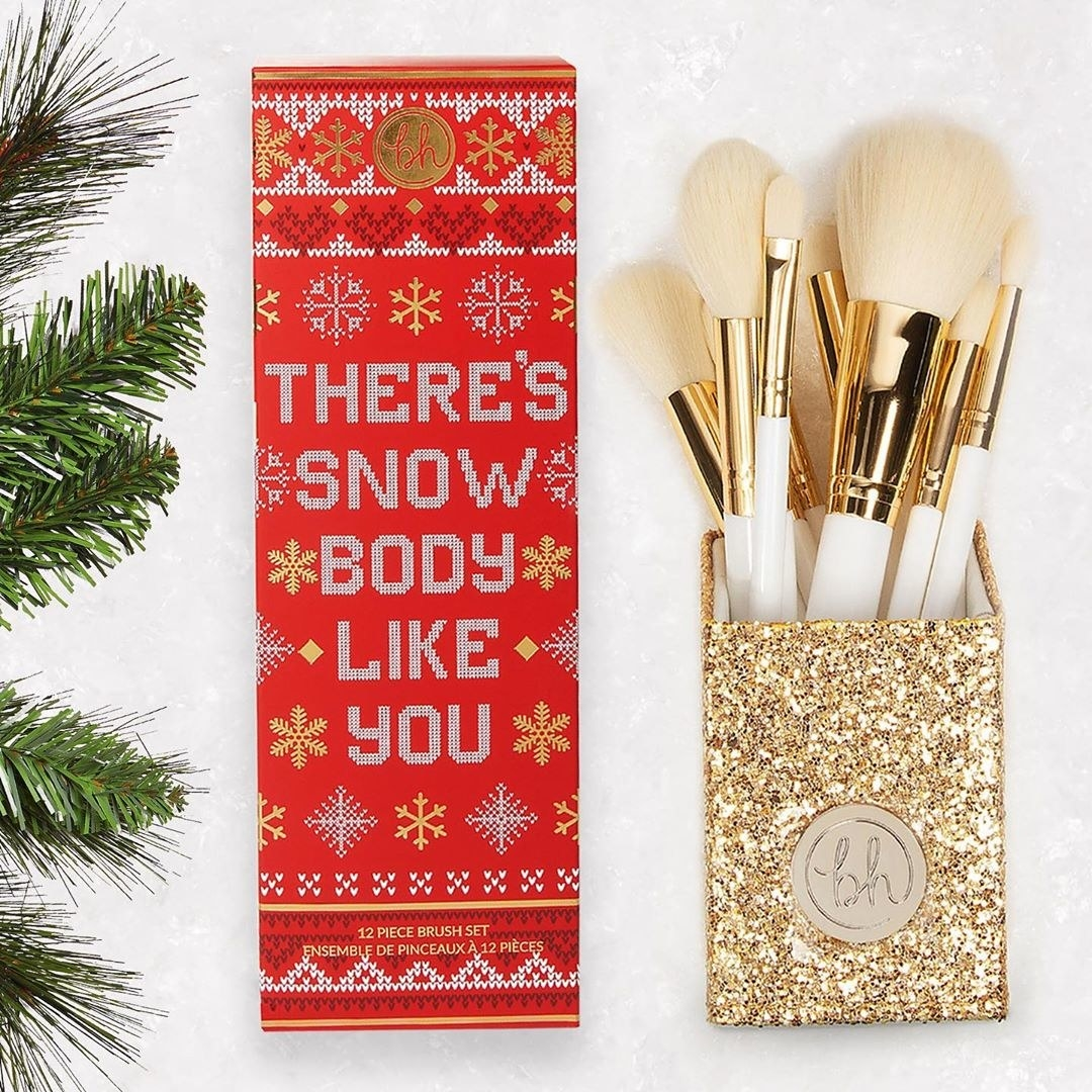 """The white brushes in their gold holder, next to the red gift box that says """"there's snow body like you"""""""
