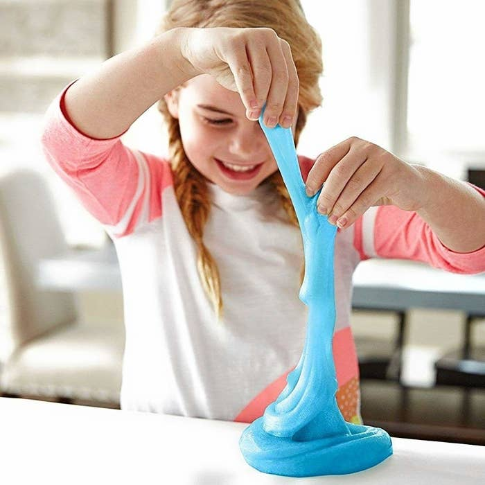 A child plays with blue, stretchy slime that they made with the ingredients in the kit