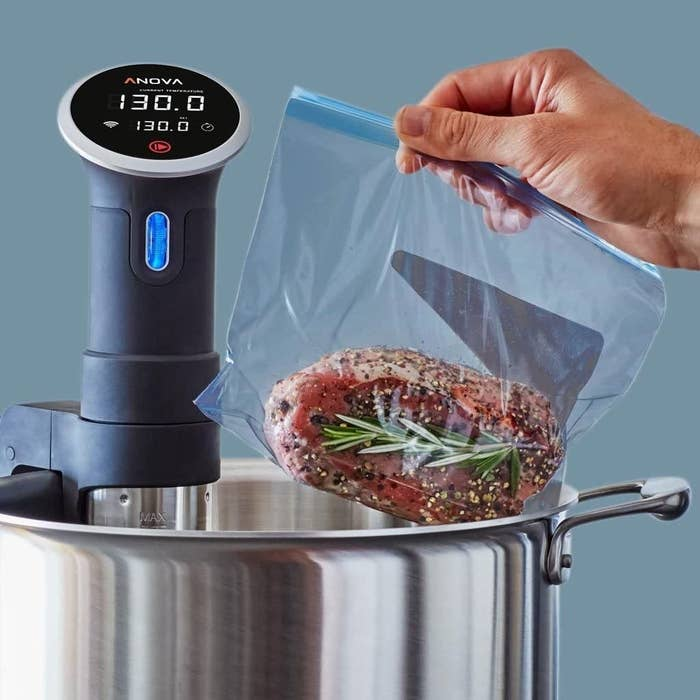 Meat, marinated in a plastic bag, being placed into a sous vide precision cooker