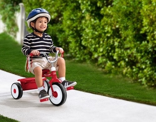 The tricycle, which has a small trunk area in the back, and which can be pedaled by a child of around three years of age