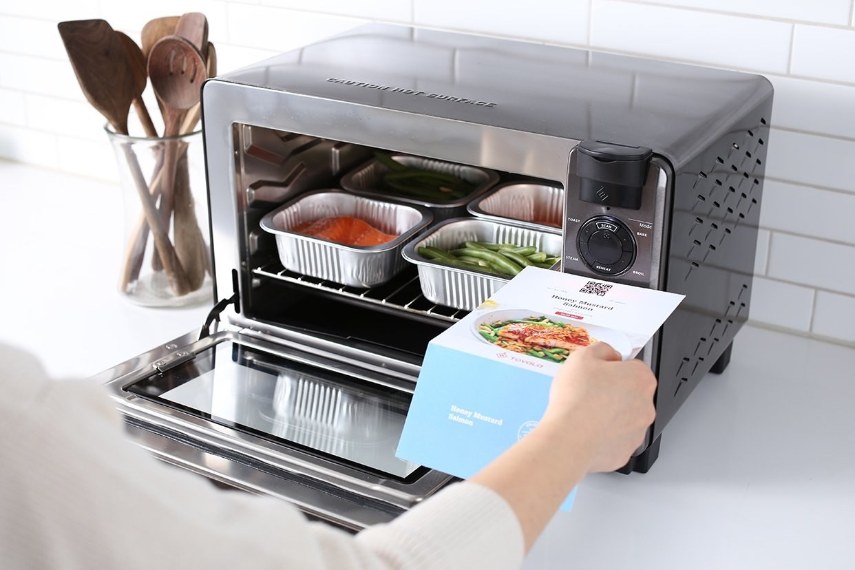 A person's hand reads operating instructions for a smart oven that sits atop a white counter next to a clear utensil crock with wooden spoons