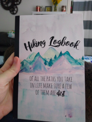 hand holding the logbook with a watercolor mountain motif on the cover