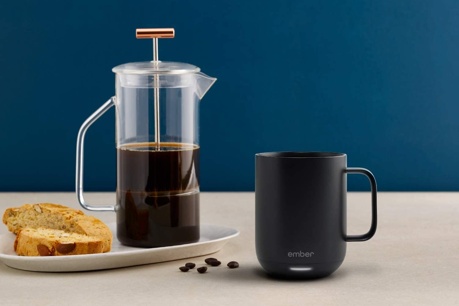 Smart mug sitting next to loose coffee beans, biscotti, and a French press