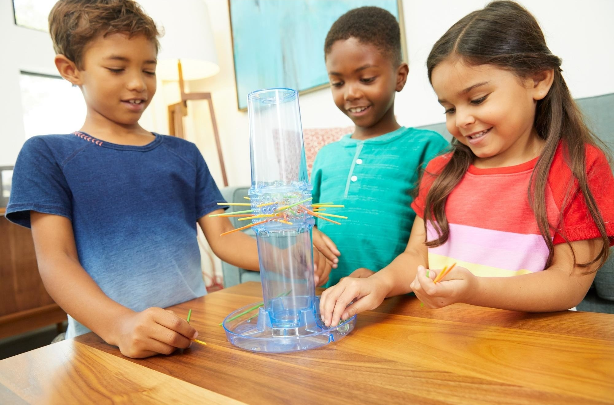 The game, which involves a large clear tube—players must insert sticks through the middle to create a dam, with the goal of keeping marbles from falling through