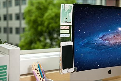 Close crop image of a desktop computer in front of a window; attached to the monitor is a clear memo board / phone holder