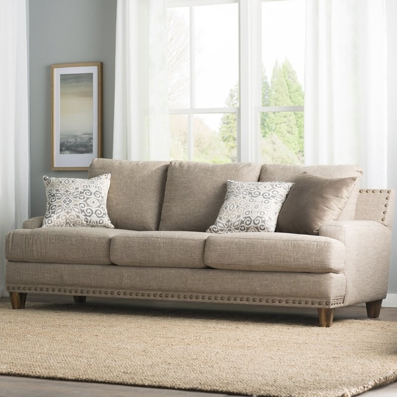 An overstuffed neutral gray couch with nailhead detail