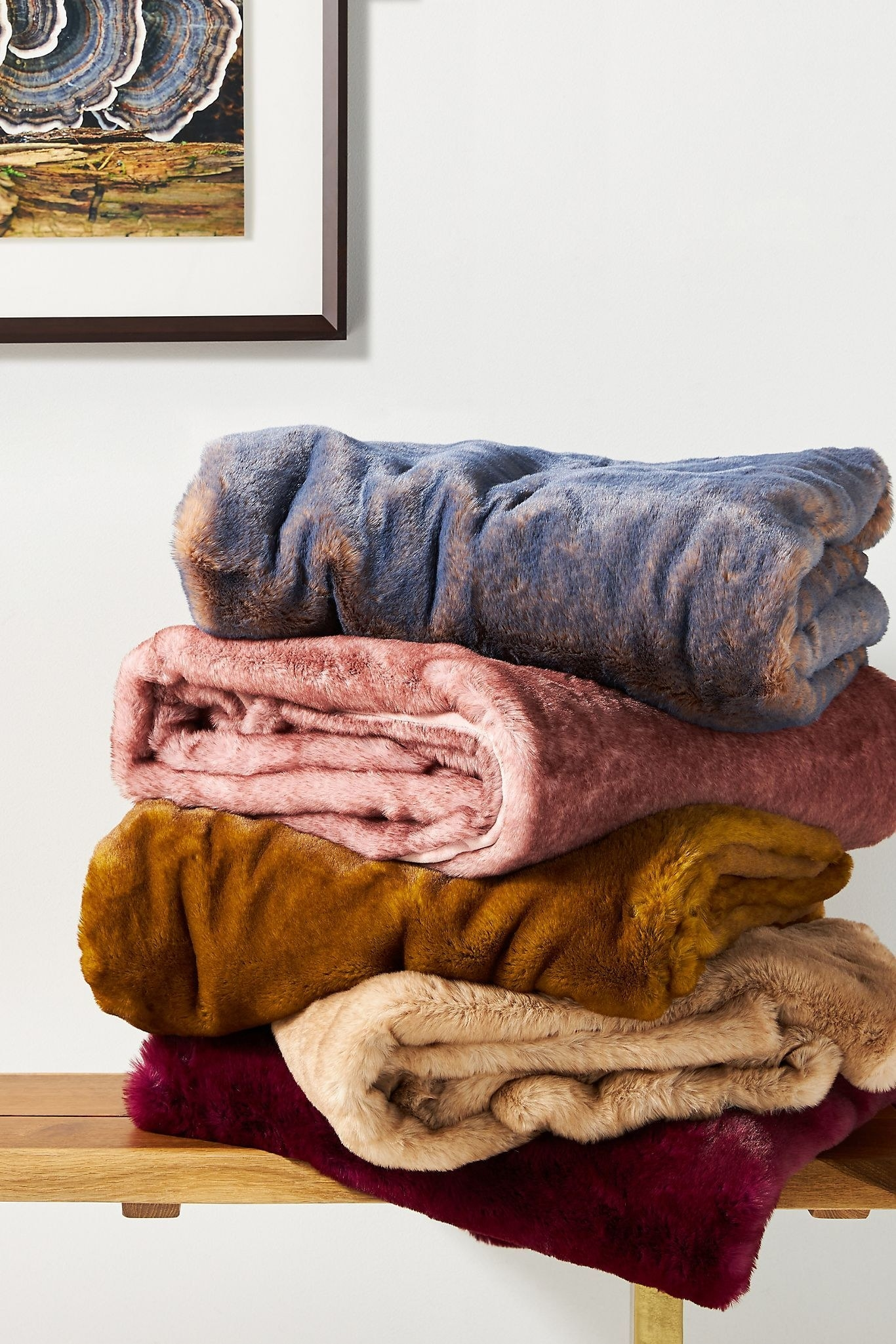five different colored throw blankets stacked on top of each other