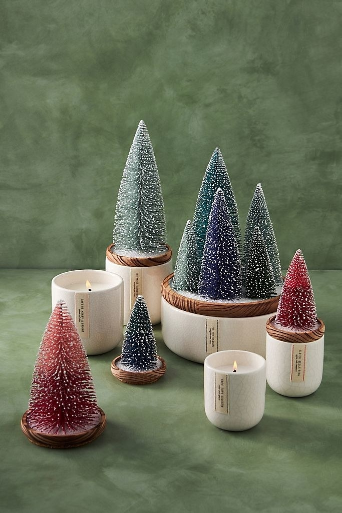 candles with frosted trees in various colors on the candle lids