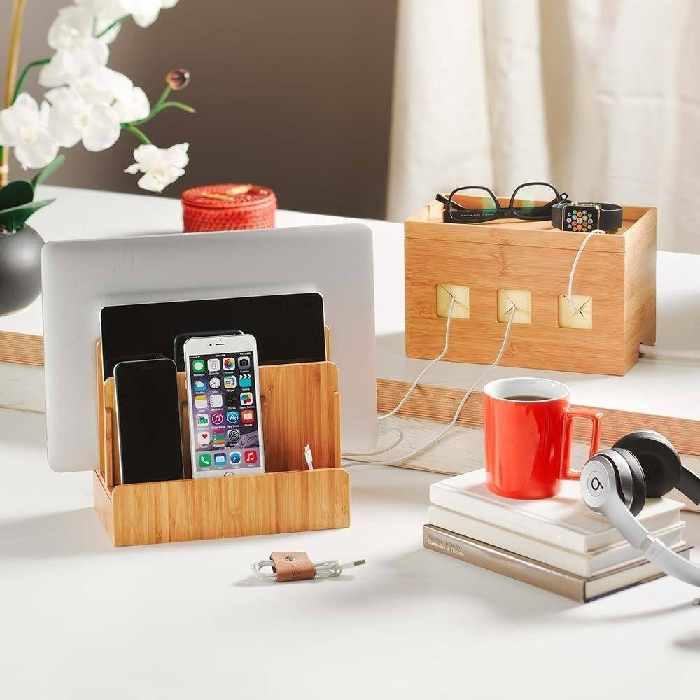 Wooden device charging station on a multilevel surface alongside wires, books, flowers, headphones, a container, and a mug of coffee