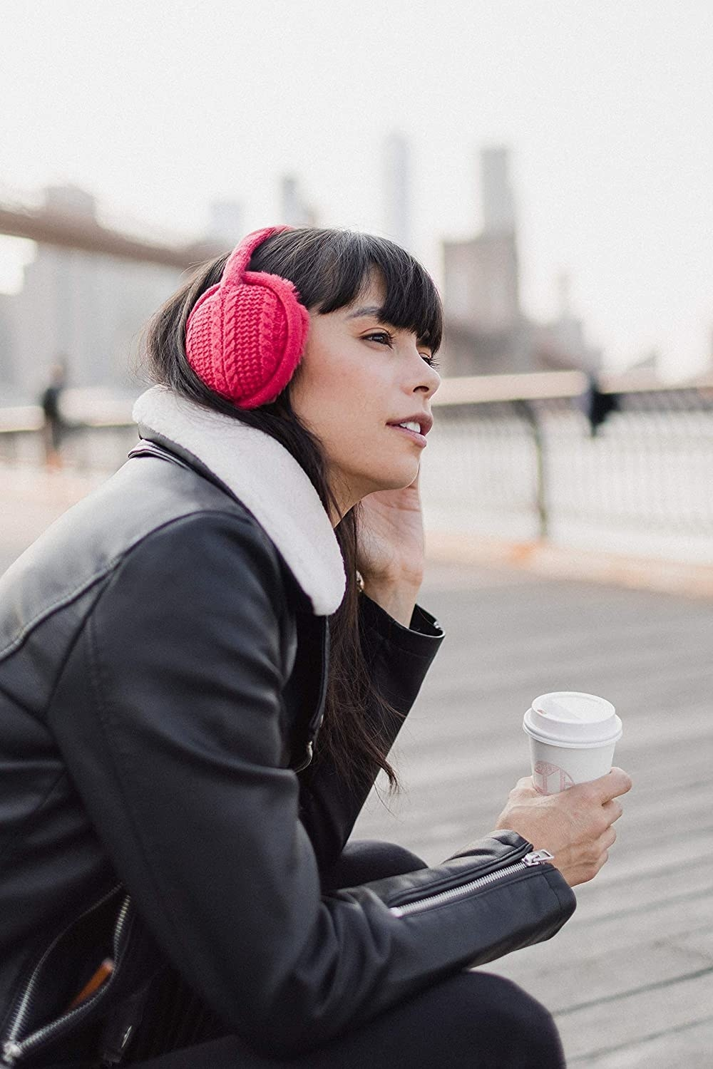 A model in the read headphones with a knit exterior and fluffy interior