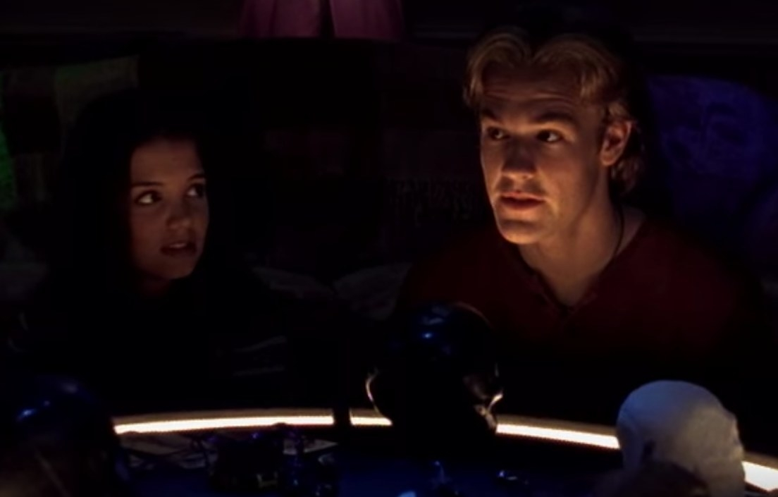 Dawson and Joey sitting in a dark room at a table, lit from below
