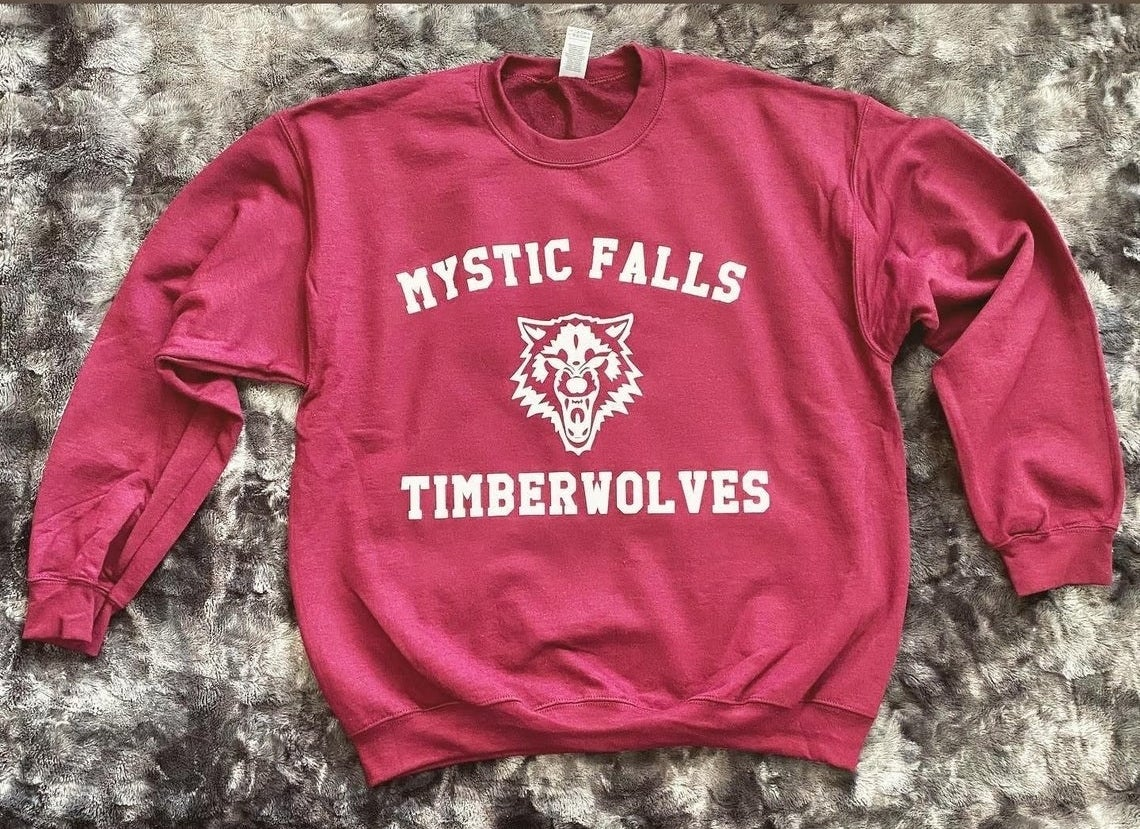 crewneck sweatshirt that says mystic falls timberwolves with a wolf in the center