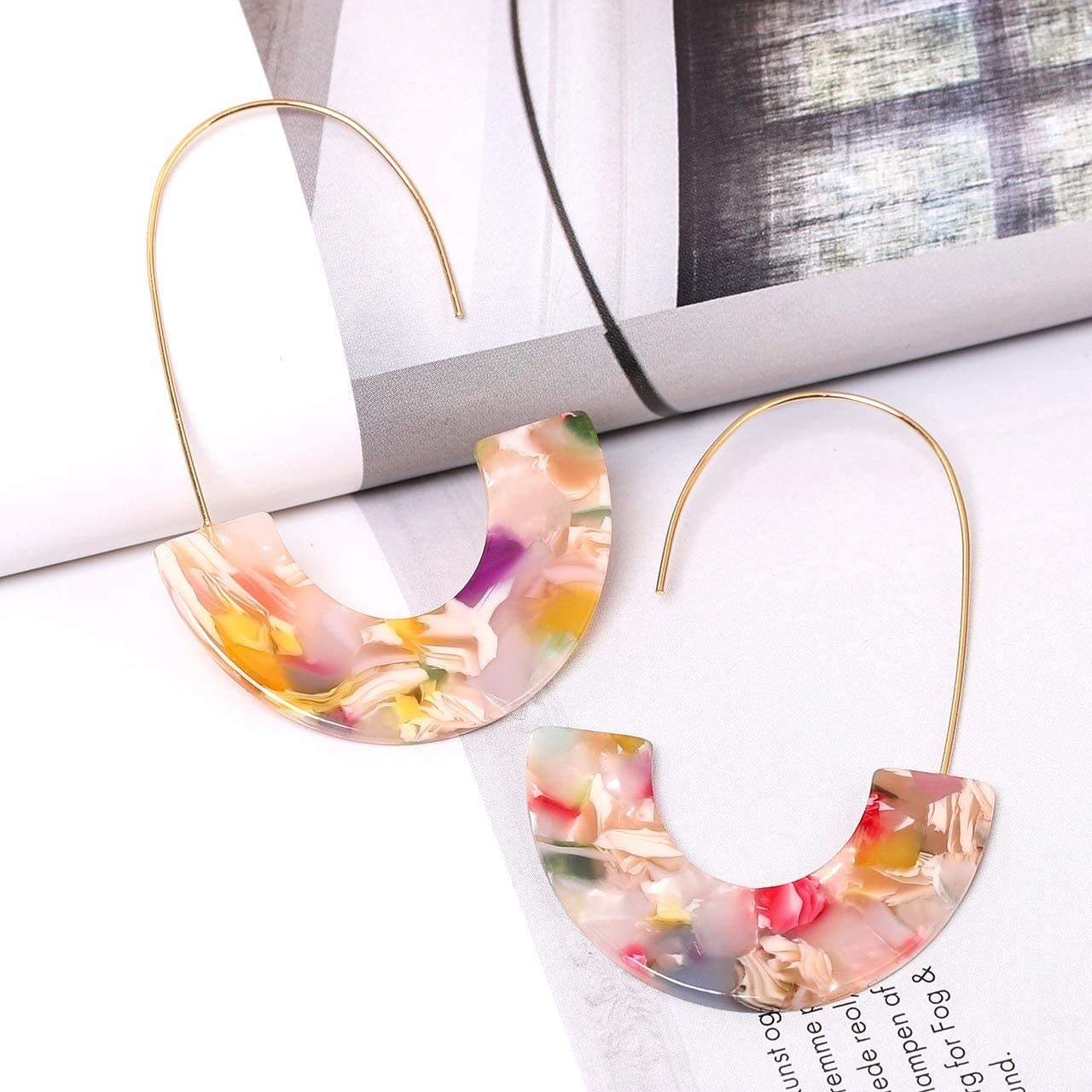 The earrings, with gold wire hooks and half-moon multicolor resin hanging from them