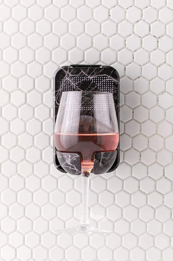 The black marble print caddy holding a wine glass on a tile wall