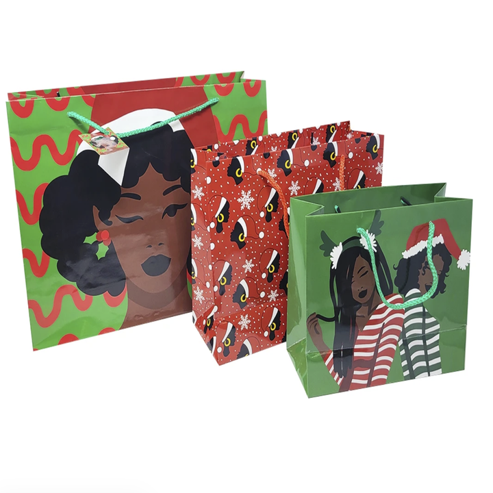 three gift bags. The first (and largest) has a dark brown woman with mistletoe earrings, an afro, and a Santa hat. Middle bag has a small black women all over with hoops and Santa hats. Smallest bag has two black girls with Santa hats and reindeer ears.