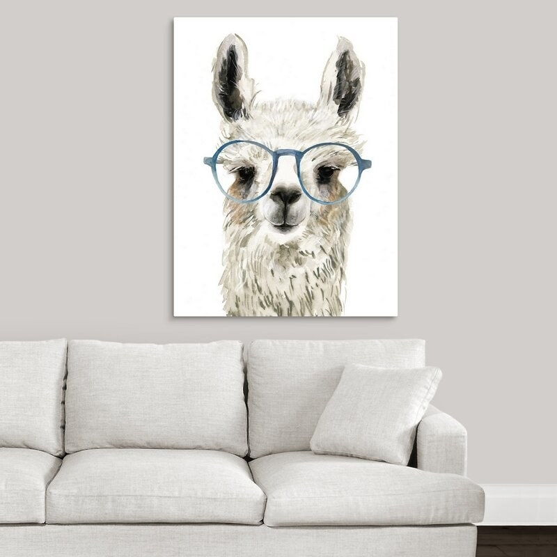 A llama canvas print wearing blue eyeglasses hung above a couch