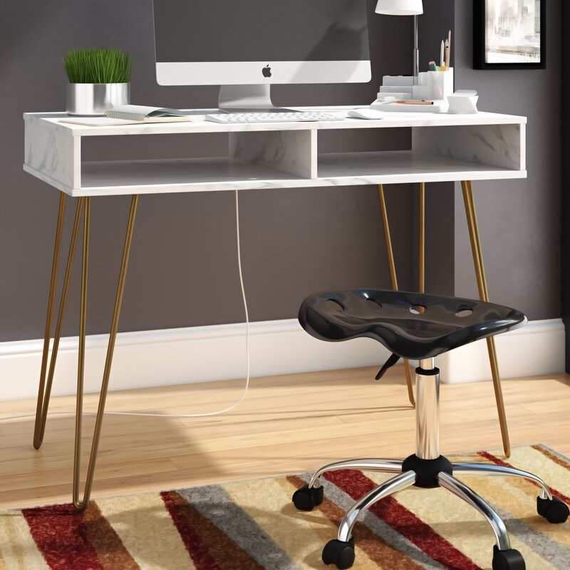 A white marble writing desk with gold chrome hairpin legs