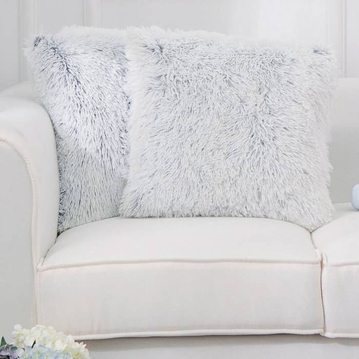 Two white furry pillows on a couch
