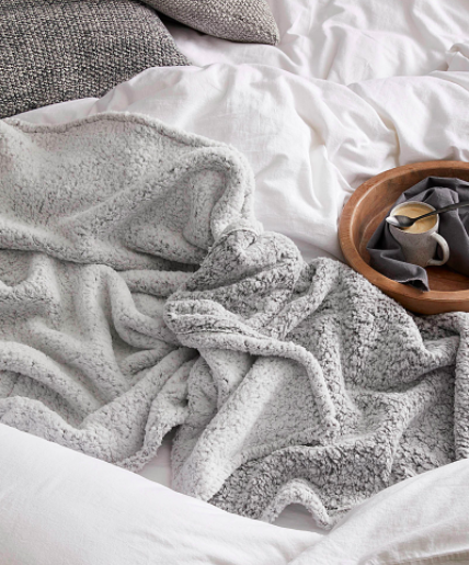 The double-sided blanket draped over a bed