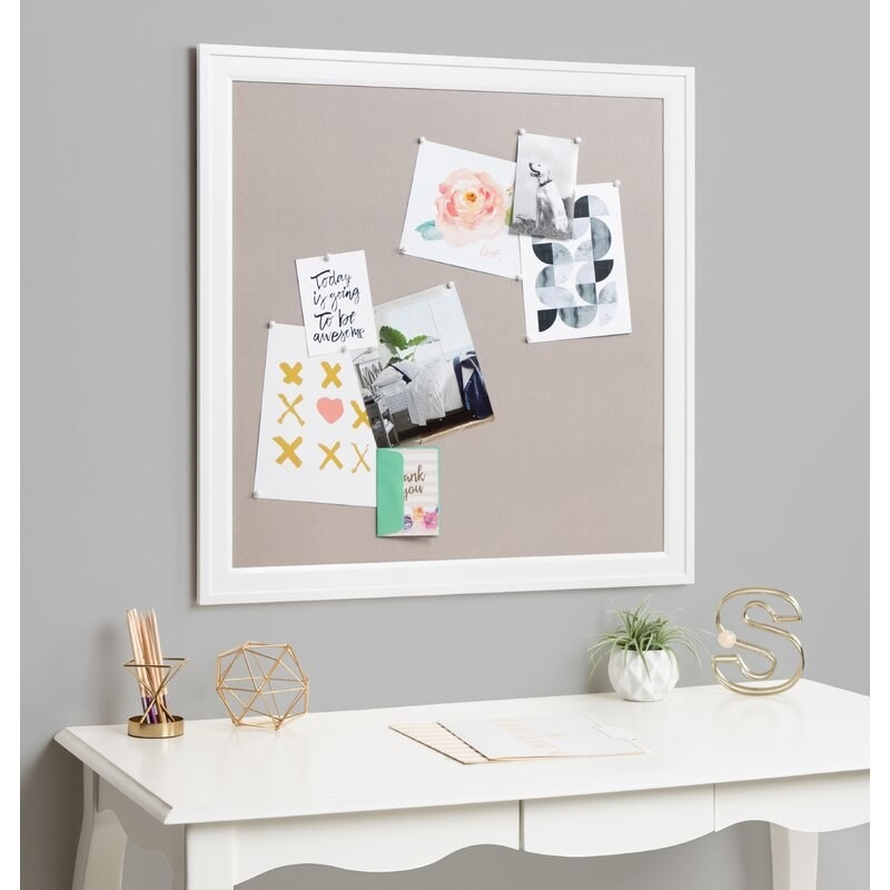 A bulletin board with a white frame and a few photos pinned on
