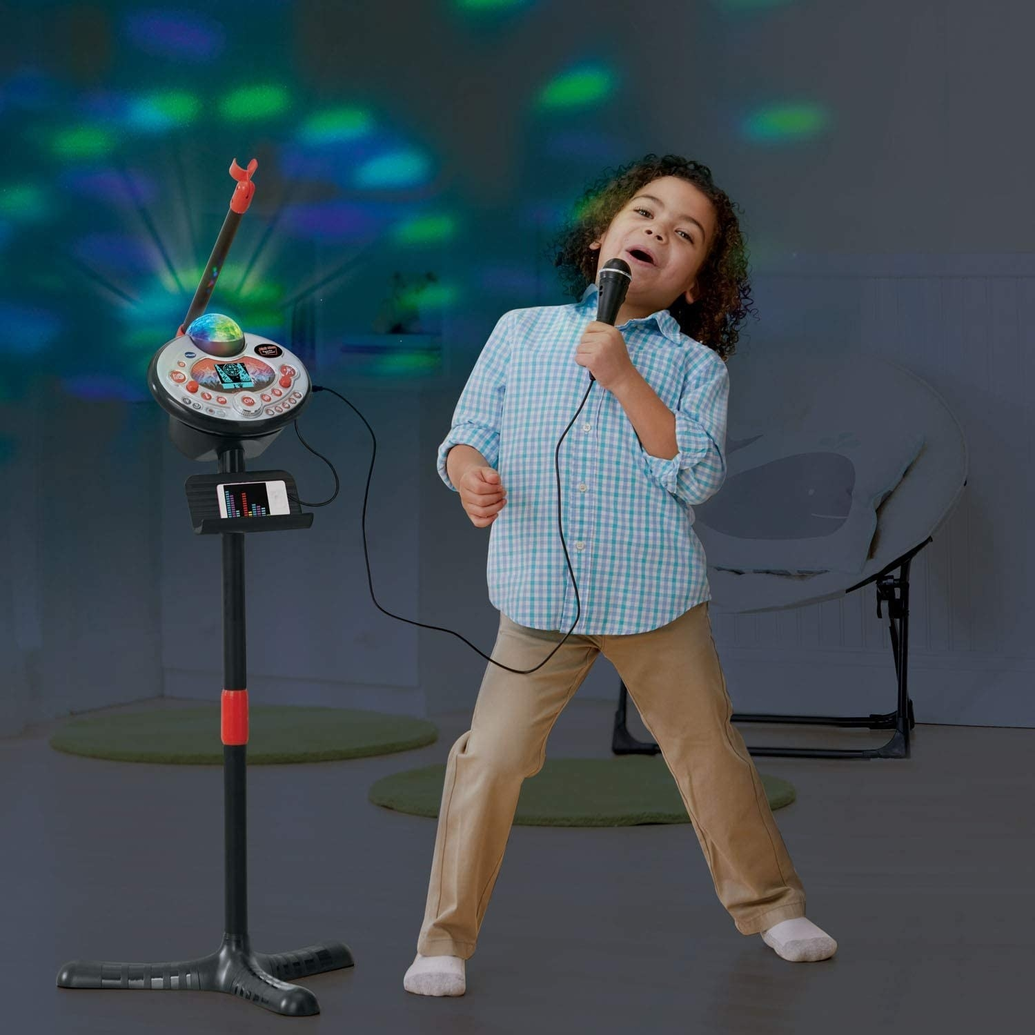 A young boy sings into a handheld microphone and karaoke set.