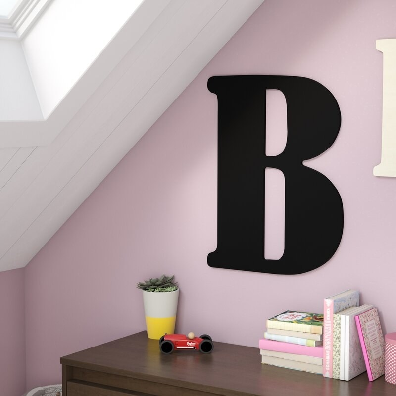 A black letter B hanging on a pink wall