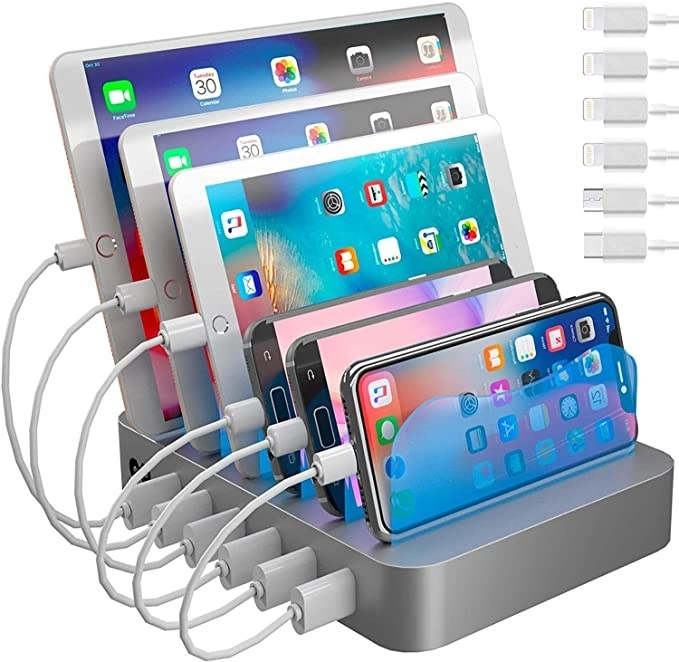 Silver charging station with three cell phones and three iPads all plugged in and lined up together