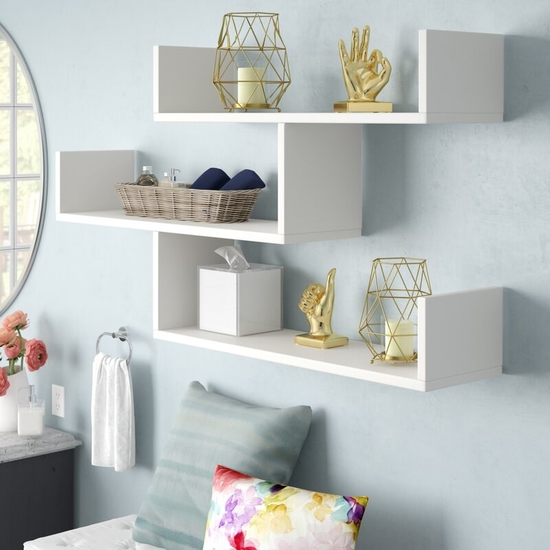 A white three-piece accent shelf with decor on top