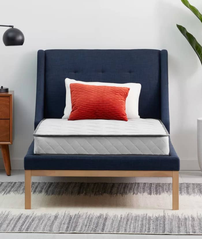 The firm innerspring mattress on a bed frame
