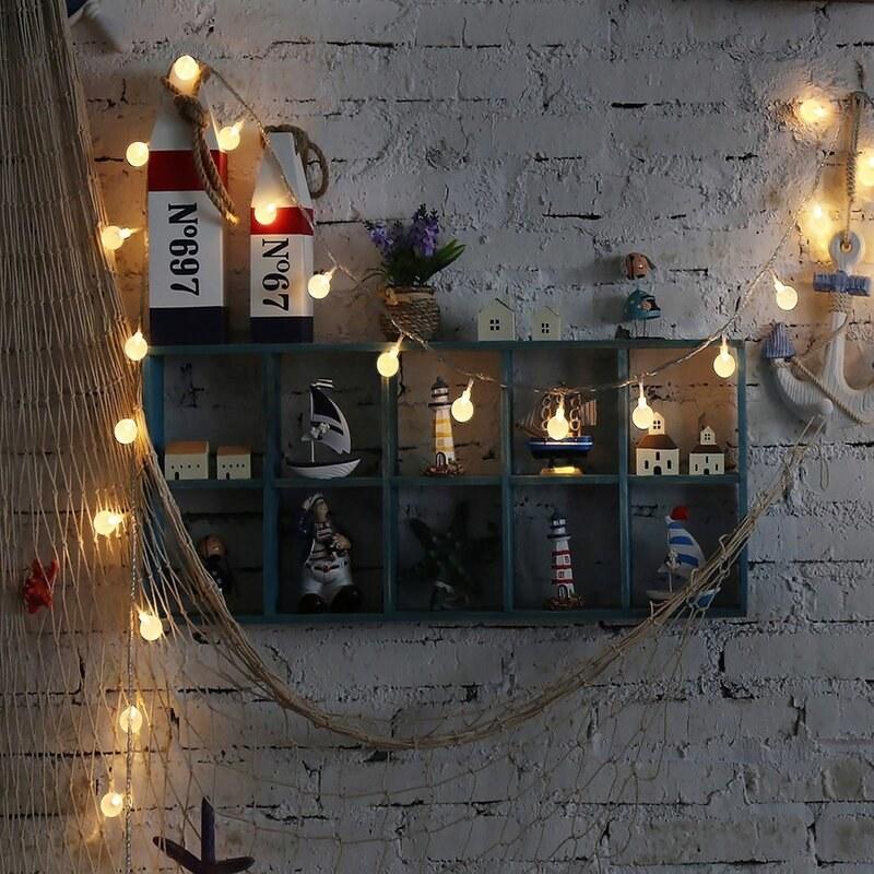 A globe string light is strung on a shelf with decor