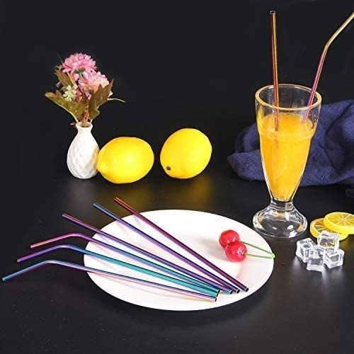 The set of rainbow coloured steel straws resting on a plate