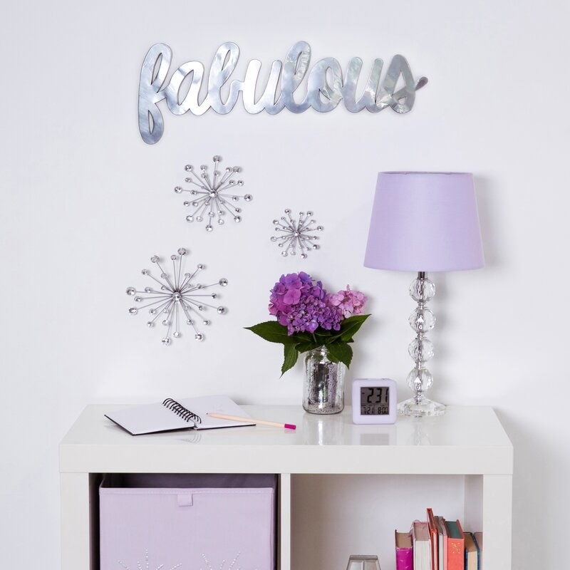 """A silver metallic sign that says """"fabulous"""" hung up on a wall"""