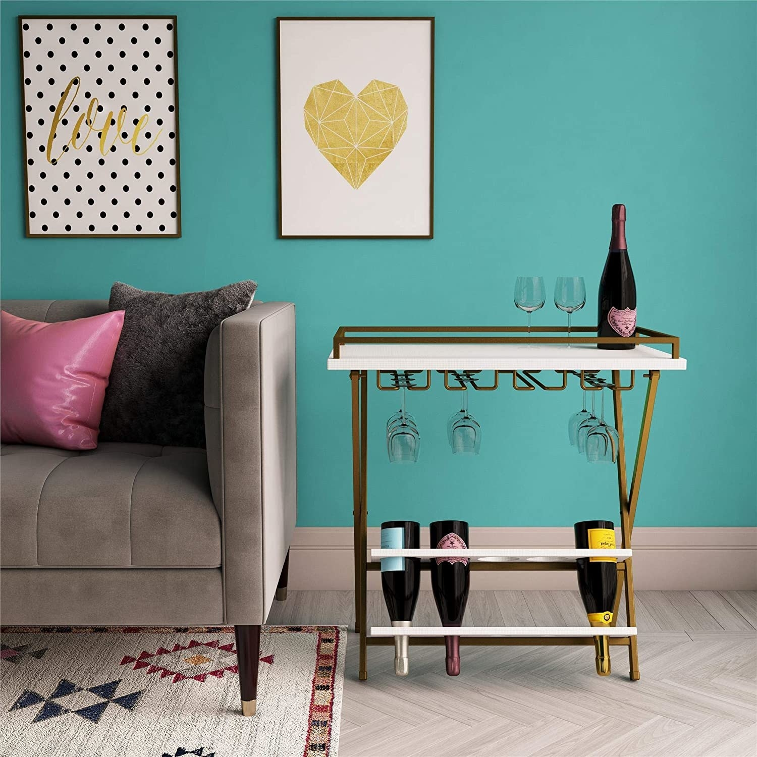 A gold bar cart with a white top and gold hinges at the bottom to hold wine glasses